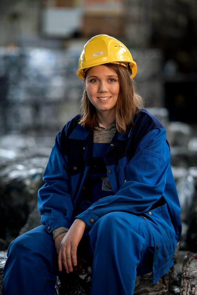 Eine Mitarbeiterin mit gelbem Schutzhelm sitzt auf einem Metallblock.
