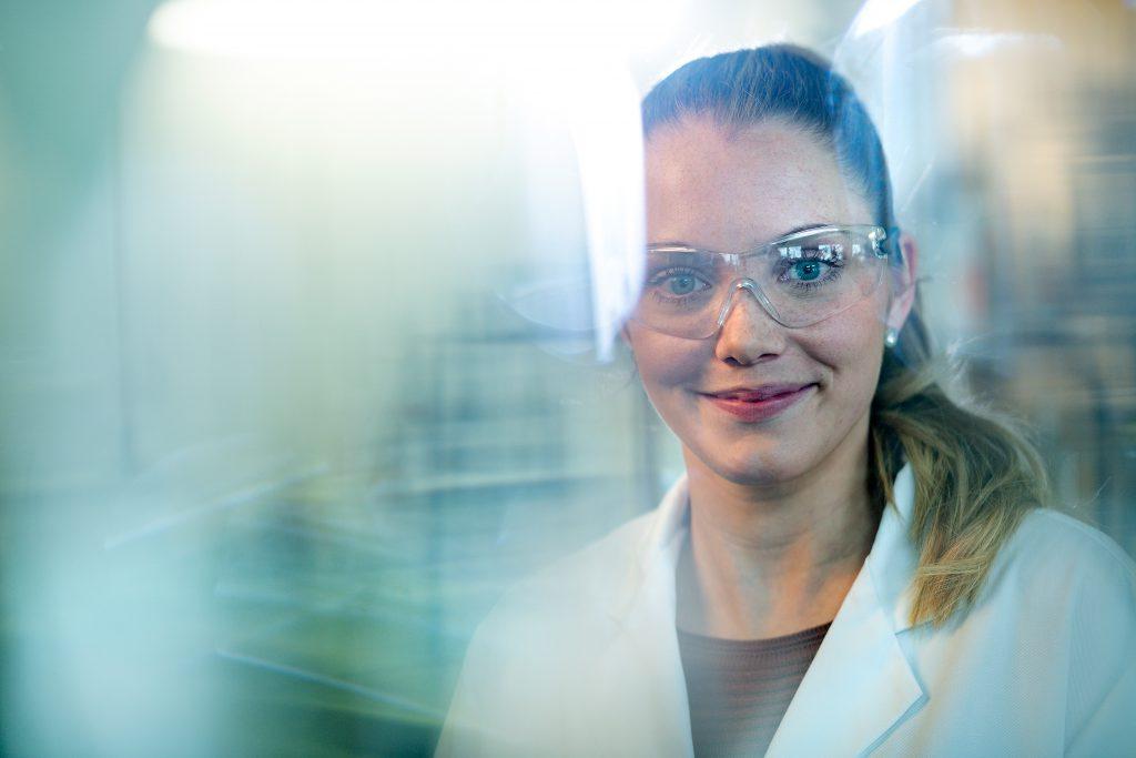Eine Frau mit Schutzbrille und weißem Kittel