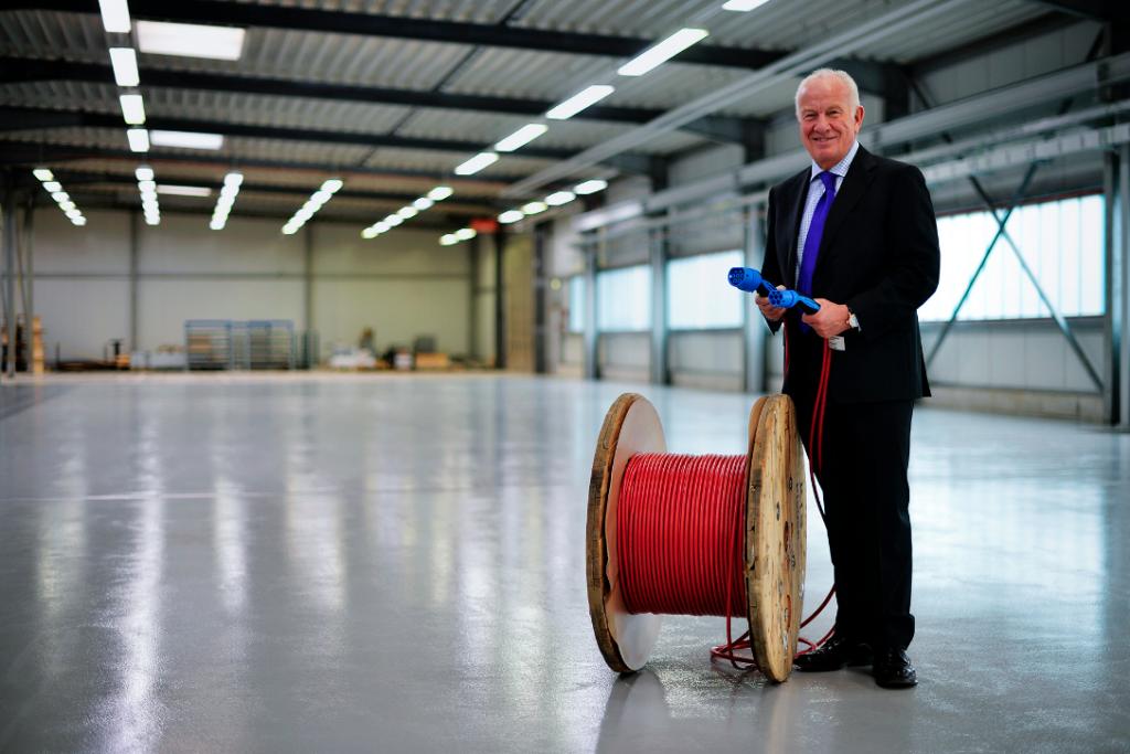 Ein Manager im Anzug hält in einer Industriehalle zwei Starkstromkabel in der Hand.